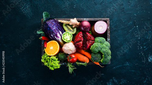 Foto Murales Fresh vegetables and fruits in a wooden box on a black background. Organic food. Top view. Free copy space.