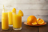 Glasses of Fresh Orange Juice on light wooden background. Side view