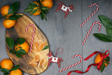 Christmas concept - board with tangerines with leaves, candy canes and decorations in the form of horses