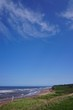Prince Edward Island, Canada: A red sandstone beach under a clear blue sky on the north shore of Prince Edward Island, in the Gulf of St. Lawrence.