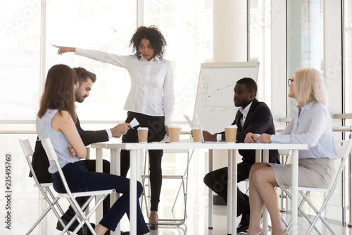 Leinwandbild Motiv Angry mixed race manager team leader firing incompetent employee intern for bad results asking to leave group office meeting having conflict or dispute, racial discrimination at work concept