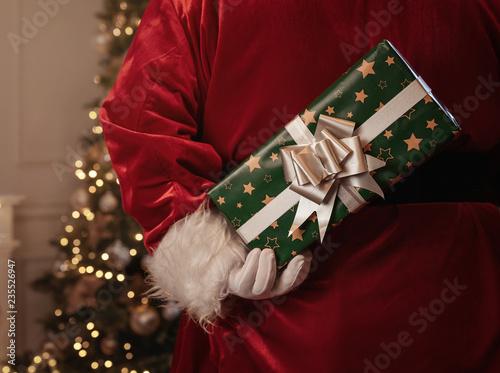 Święty Mikołaj trzyma boże narodzenie prezent za jego z powrotem