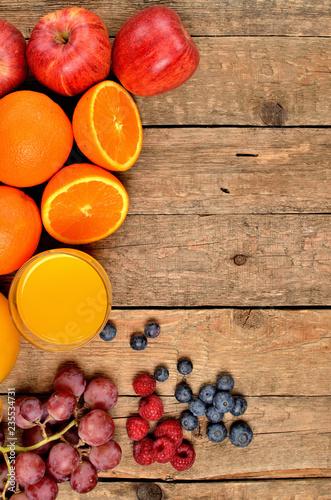 Sok pomarańczowy, świeże pomarańcze, jabłka, winogrona, maliny i jagody na drewnianym stole - widok z góry - zdjęcie w pionie - lewa ramka orientacyjna