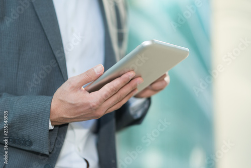 Businessman using his tablet - 235548935