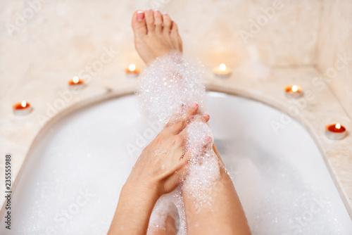 Nogi kobiety w pianki do kąpieli. Relaks w spa.