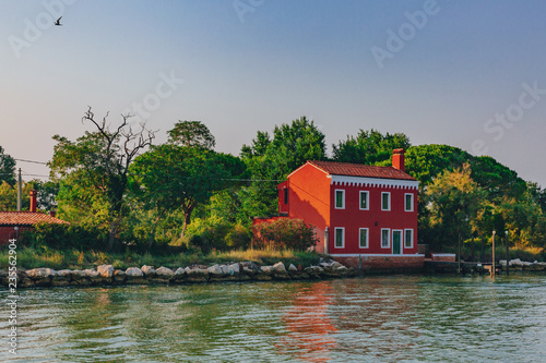Red house by trees and water near the island of Burano, Venice, Italy