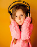 Little girl with headphones on yellow background