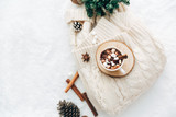 Flat lay hot cocoa with marshmallow ant knitted sweater with christmas decorations. Cozy holiday concept