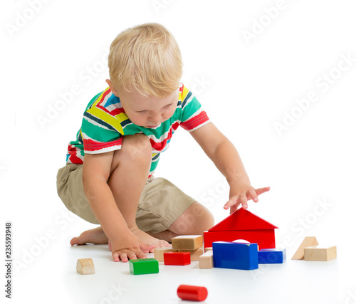 Leinwandbild Motiv Child boy building castle with colorful wooden cubes, isolated on white