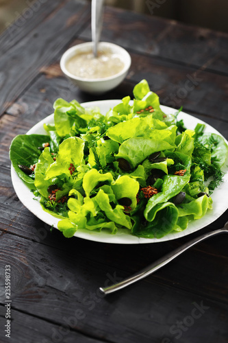 Plate green salad wooden table Healthy dietary food - 235598733
