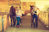 Cowgirl and jockey walking with horses in stable © Voyagerix