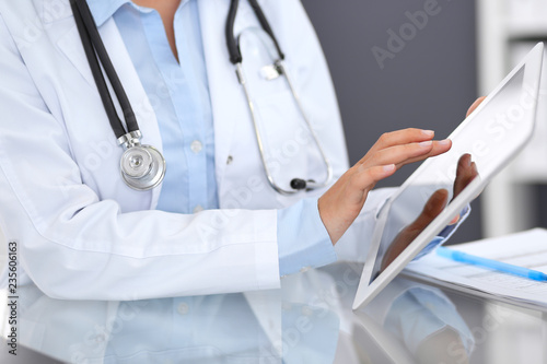 Close-up of female physician hands using digital tablet  while sitting at glass desk at hospital office. Medicine and healthcare concept - 235606163