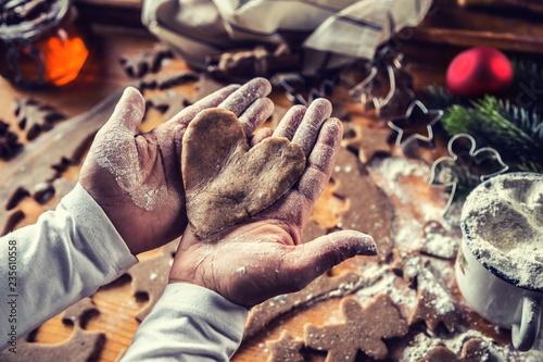 Leinwanddruck Bild Christmas baking and gingerbread heart in woman hands