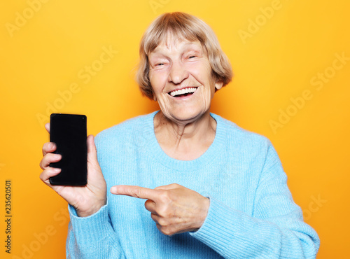 Leinwandbild Motiv A picture of mature woman with new smartphone.