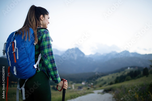 Young woman hikes in the mountain with beautiful view - 235628976