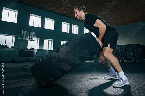Bez koszuli młody dysponowany mężczyzna podrzuca ciężką oponę przy gym. Ćwiczenie, fitness, sport, trening, sportowiec, moc, trening, pojęcie kulturystyki