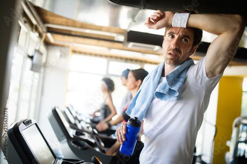 Przystojny sportowy mężczyzna odpoczywa, po przerwie robi ćwiczeniu