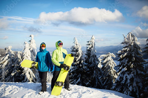Leinwanddruck Bild Two snowboarders posing at ski resort. Riders friends carrying their snowboards through forest for backcountry freeride and wearing reflective goggles, colorful fashion outfit. Copyspace area.