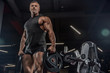 Leinwanddruck Bild - handsome man with big muscles trains in the gym, exercises
