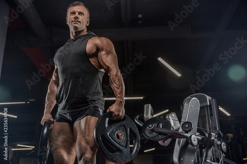 Leinwanddruck Bild handsome man with big muscles trains in the gym, exercises