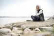Quadro  Beautiful elderly woman sitting by the ocean in sportswear