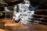 Female splashing her feet in cascading waterfall