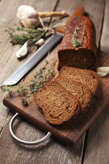 Dark bread on wooden cutting board with herbs.
