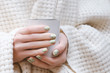 Female hands with glitter nail design holding white cup.