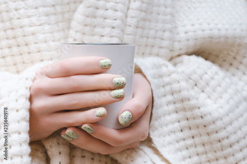 Female hands with glitter nail design holding white cup. - 235640978