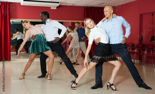 Portrait of positive adult pairs enjoying tango in modern dance hall