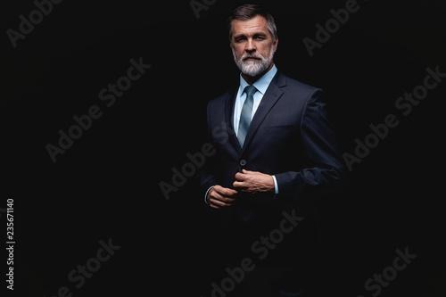 Leinwandbild Motiv Handsome mature business man isolated on black background