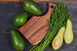 Healthy green food background with copy space for text. Fresh organic avocados and dill around wooden board. Raw ingredients for veggie salad or diet dish. Top view - 235673549