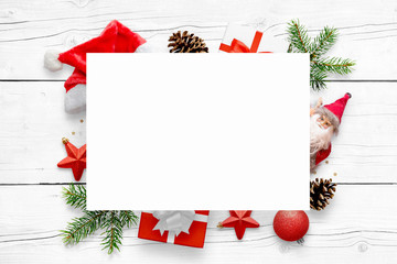 New Year's scene with free space for greeting text on white paper and Christmas decorations in background. White wooden table in background.