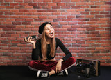 Photo of joyous young hip hop girl, sitting on floor against brick wall with boombox and spray paint