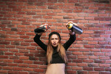 Image of active hip hop girl 20s, standing against brick wall with spray cans