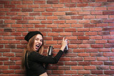 Image of stylish hip hop girl 20s, drawing on brick wall with spray paint