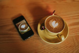 Cup of coffee with a heart in the foam, with a mobile phone next to it, on a wood table.