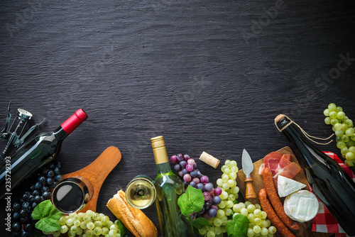 Wine bottles with grapes, cheese, ham and corks - 235729393