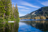 White boat with green trim reflected in calm blue alpine lake tied up to a shoreline of tall pine trees in California's Sierra Nevada mountains