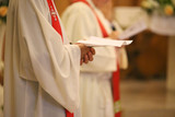 priest with hands joined in prayer during Holy Mass in church
