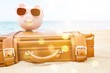 Pink piggy bank in sunglasses on leather travel case over sea