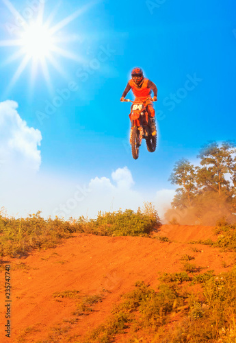 Active sports background - jumping motorcycle rider silhouette, blue sky, bright sun