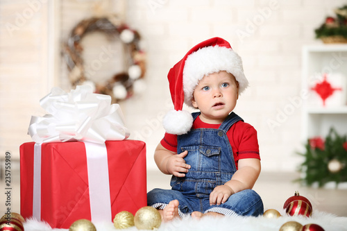 Foto Murales Baby boy with baubles and gift box sitting on floor at home