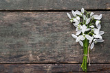 Bouquet of snowdrop flowers on grey wooden table
