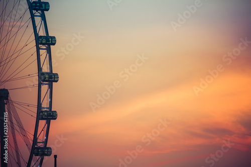 A close up of a Ferris wheel with the clouds behind it colored by the morning light.