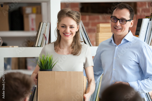 Leinwandbild Motiv Smiling team leader, hr manager, friendly boss, executive introducing new just hired female employee to colleagues, happy woman holding box with belongings, first day at work concept