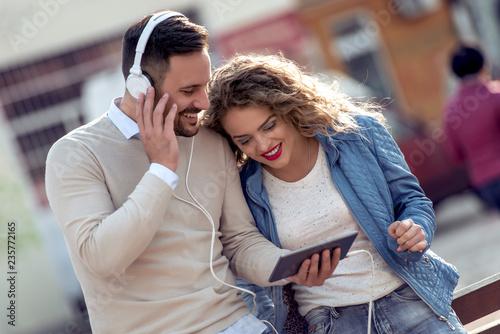 fototapeta na ścianę Couple listening to music outside on the tablet