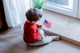 Little baby boy with USA flagg sitting on a floor at home