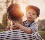 Beautiful portrait of a cute little boy hugging his dad - 235785583