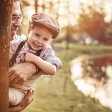 Beautiful portrait of a cute little boy hugging his dad - 235785961